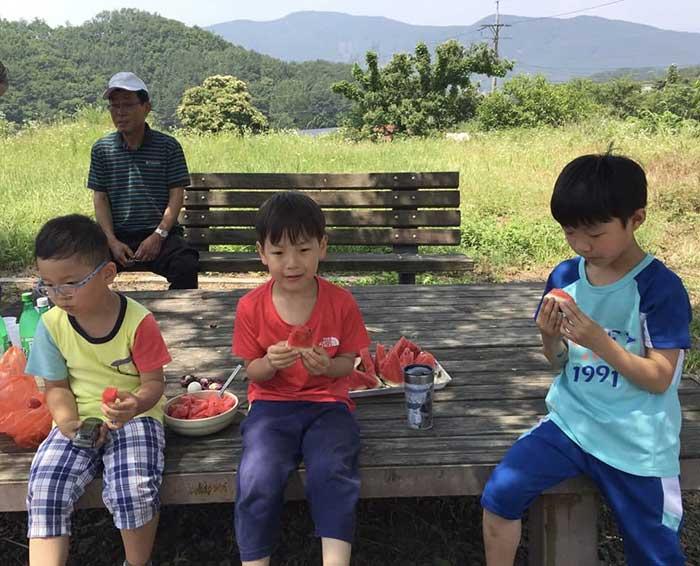 2016년, 마을회관 청소 후 밤만디에 앉아 시원하게 수박을 먹는 아이들.