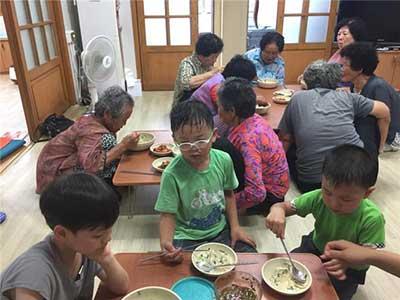 마을어른들과 함께 콩국수를 먹는 아이들.